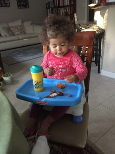 getting a snack in her high chair